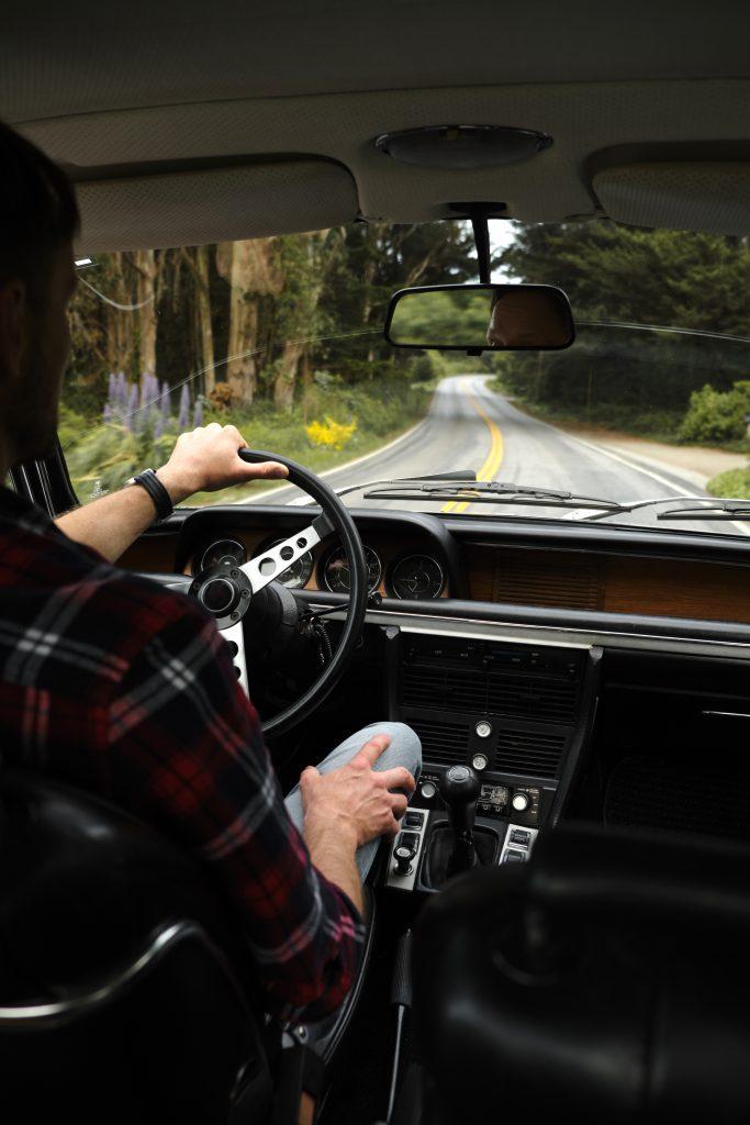 Crop unrecognizable traveler driving car on asphalt road in countryside